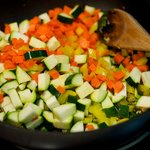 Stir in yellow bell peppers, carrots, and zucchini,