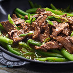 Quick, easy marinated ginger beef strips. Asian inspired steak strips glazed in a ginger honey soy sauce with green peppers served over rice.