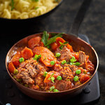 Tender chunks of beef, slowly braised in tomatoes with carrots and peas. An easy delicious stove-top beef dinner.