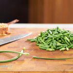 Prepared garlic scapes; trimemed and chopped on a wood cutting board with a chef's knife and pine nuts. z To prepare garlic scapes; trim off the tough top above the bulbous tip and trip the bottom.