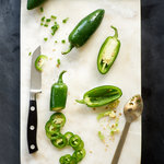 Preparing jalapeno peppers on a marble slab.  Sliced jalapenos, diced jalapenos, how to seed jalapeno peppers. Overhead glossary style.