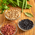 Dried black beans, light red kidney beans, grabanzo beans (chickpeas), green beans, parsley and bay leaf with shallow depth of field on a wood grained background.