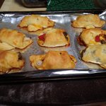 Crescent rolls stuffed with ground beef, white onions, whole peeled tomatoes, and shredded cheddar cheese.