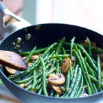 Green beans are heated through and mixed in the skillet with the other ingredients and ready for plating.