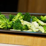 Place the seasoned broccoli onto the baking sheet.