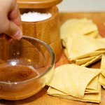 Make the dressing for the chips and cut the tortillas into wedges.