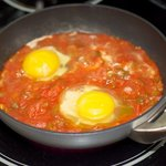 Crack eggs into the poaching liquid (the salsa)