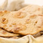 Place the naan bread in a basket and serve with or without any butter brushed on top