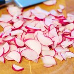 then half and thinly slice the radishes...