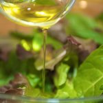 Drizzle the olive oil over the mixed greens in a large bowl.