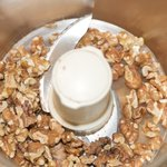 Add lightly toasted walnuts into a food processor.