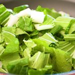 Add the bok choy into a hot wok or a large skillet with vegetable oil.