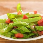Add the snow peas, red bell pepper and garlic to a hot skillet with 1 tablespoon of vegetable oil added,