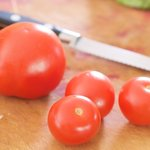 Get a few beautiful tomatoes washed and dried, set them on the cutting board.