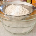 Add the flour, baking powder, and baking soda into a fine sieve over a large bowl.