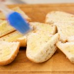 Brush the garlic-olive oil on each slice.