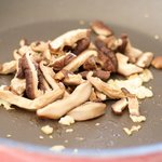 Add the mushroom slices into the hot skillet with oil, ginger, garlic and scallions,