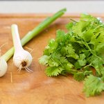 Start to work on chopping up the final two vegetables, scallions and cilantro.
