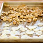 Place the walnut pieces and garlic slices onto a baking sheet.