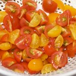 Quater the cherry tomatoes and put them into a salad spinner.