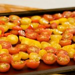 Place the halved cherry tomatoes onto a large baking sheet.