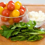 Then finely chop the fresh herbs, half the cherry tomatoes and crumble the cheese, and set aside.
