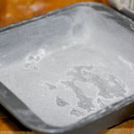 Grease a 9-inch square baking pan with butter, then flour it.