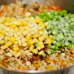Add the corn and peas into the pan,