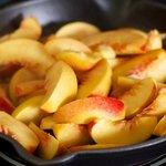Add the peaches into the hot pan with the bubbling butter.