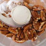 In a food processor, add 1/2 cup pecans and sugar.