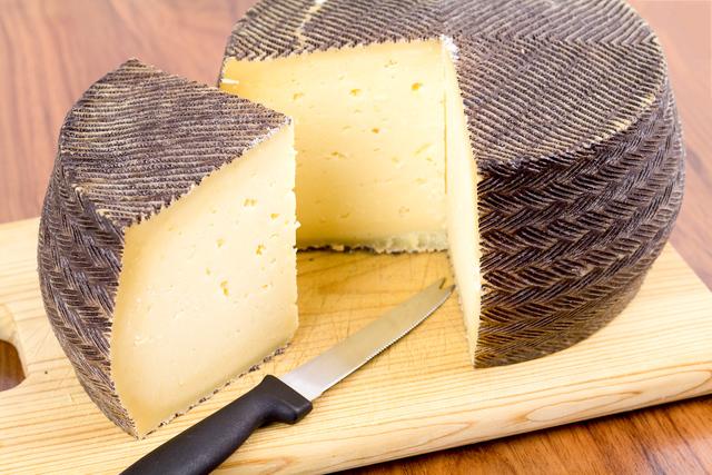 manchego cheese wheel, cut