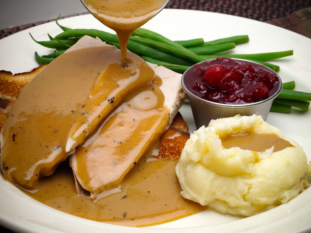 Smooth lump-free gravy pouring over turkey and mashed potatoes