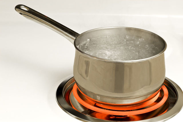 Boiling water in a pot on a red hot burner